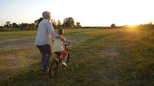 Thumbnail for Back View of Boy Learning To Ride Bike with Granny
