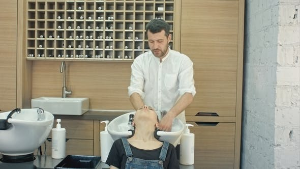 Thumbnail for Handsome Hairdresser Washing Female Hair with Concentration