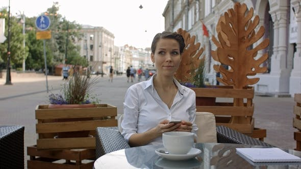 Thumbnail for Young Woman Drinking Coffee and Using Her Mobile Phone in a Outdoor Cafe