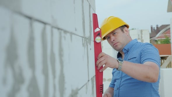 The Architect in the Yellow Helmet Using the Level Checks the Accuracy of the Construction of Walls