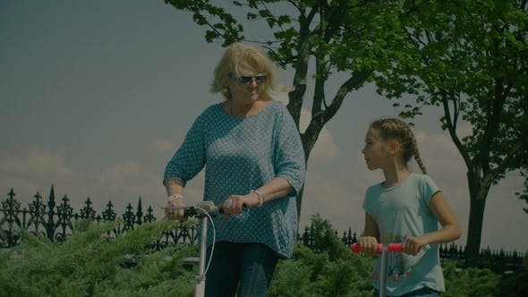 Thumbnail for Grandmom and Grandkid on Scooters Enjoying Leisure