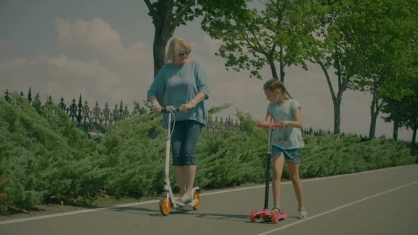 Thumbnail for Grandmother and Granddaughter Riding Scooters in Park