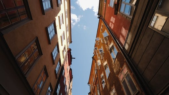 Cover Image for The Beautiful Narrow Street of Stockholm. The Open Windows Reflect the Sky and the Sun. Architecture
