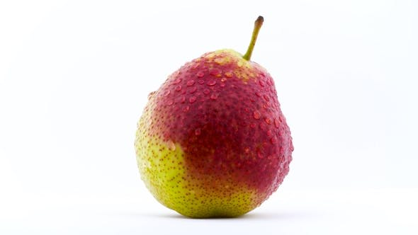 Thumbnail for One Pear Fruit in Water Drops Is Rotating on the Turntable. Isolated on the White Background. . .