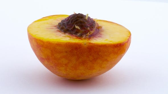 Thumbnail for One Half of Peach Fruits with a Pit. Rotating on the Turntable. Isolated on the White Background