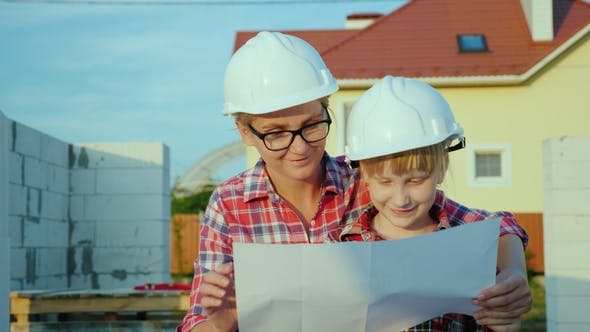 A Little Girl in a Helmet with a Young Mother Is Studying the Architectural Plan