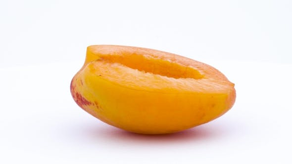 Thumbnail for One Half of Apricot Fruit Is Rotated on the Turntable Isolated on the White Background