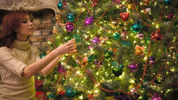 Thumbnail for Young Woman Decorating the Christmas Tree