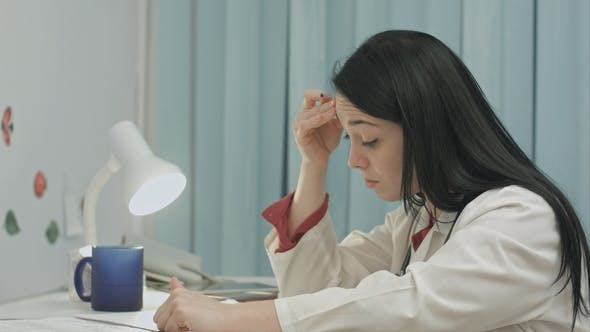 Tired Female Doctor  Writes Diagnose of Patient
