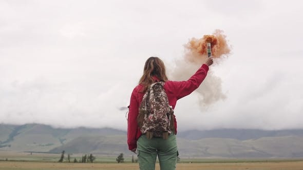 Thumbnail for Female Traveler with Smoke Sticks Gives a Sign and Attracts Attention with Colored Smoke. Tourist