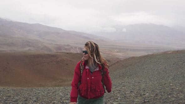 Thumbnail for Traveler in Extreme Conditions the Girl Is a Tourist Walking Along the Mountainous Terrain