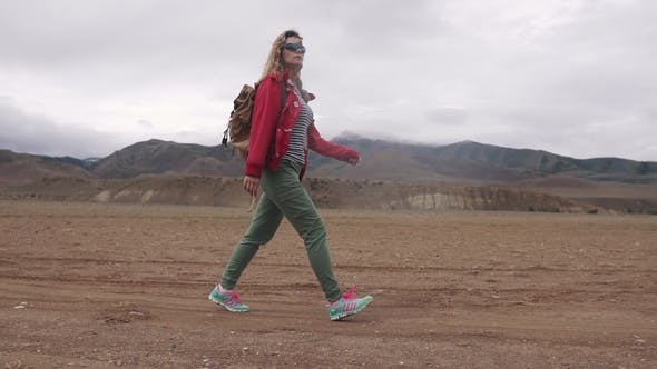 Thumbnail for Portrait of a Tourist with a Backpack in the Mountains Girl Traveler Walks the Mountainous Terrain