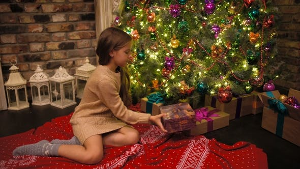 Thumbnail for Christmas Gift Surprise A Little Girl Opens a Christmas Present in Amazement