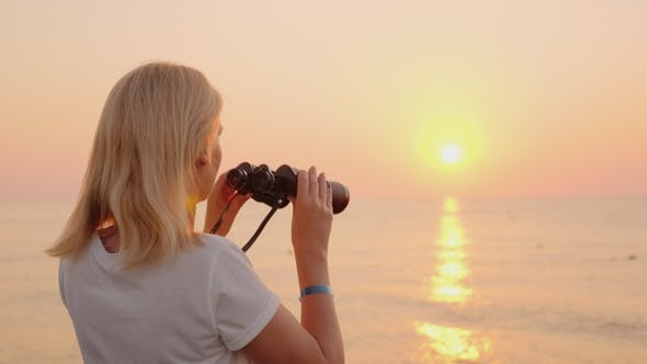 Thumbnail for Young Romantic Woman Looks at the Sunrise Over the Sea of Pink Color. Uses Binoculars