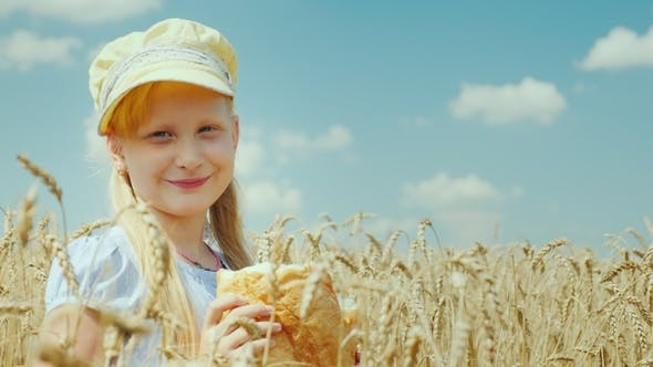 Thumbnail for A Girl with a Loaf of Bread Stands on a Wheat Field, Looks at the Camera