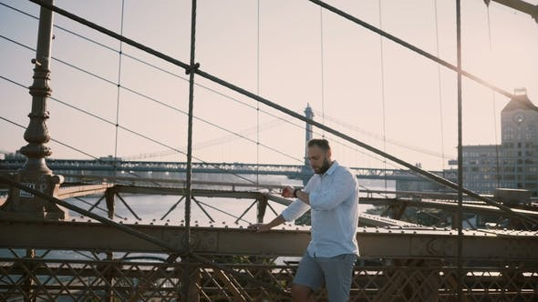 Happy Caucasian Man Stands Alone at Brooklyn Bridge Looking Away and Using Smart Watch Bracelet