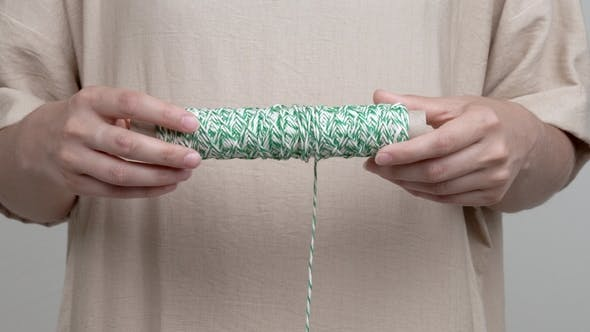 Thumbnail for Woman's Hands Are Holding a Roll with White Green String Horizontally The Rope Hangs Down