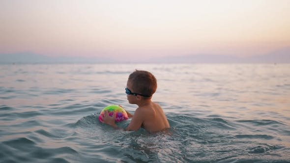 Cover Image for Child Taking Ball To Water and Then Floating on It in the Sea