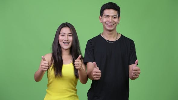 Cover Image for Young Asian Couple Giving Thumbs Up Together