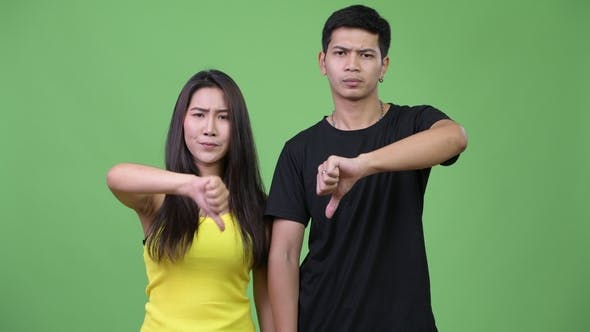 Thumbnail for Young Angry Asian Couple Giving Thumbs Down Together