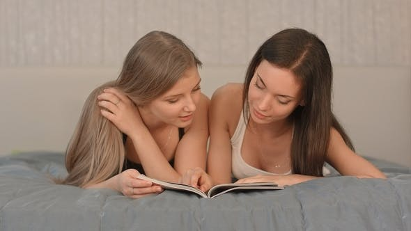 Thumbnail for Two Beautiful Women Reading Magazine at the Bedroom