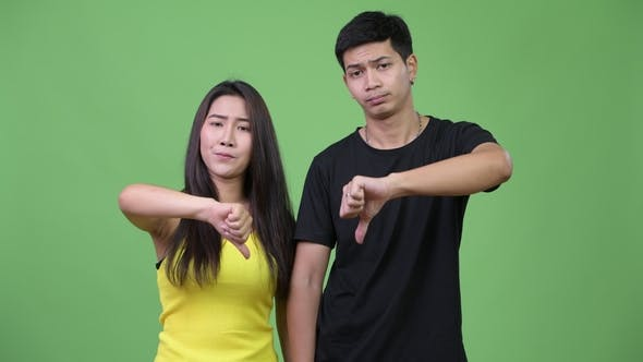 Thumbnail for Young Sad Asian Couple Giving Thumbs Down Together