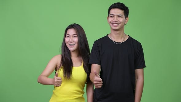 Thumbnail for Young Asian Couple Giving Thumbs Up Together