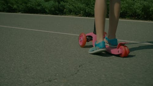 Feet of Little Girl in Sandals Riding Push Scooter