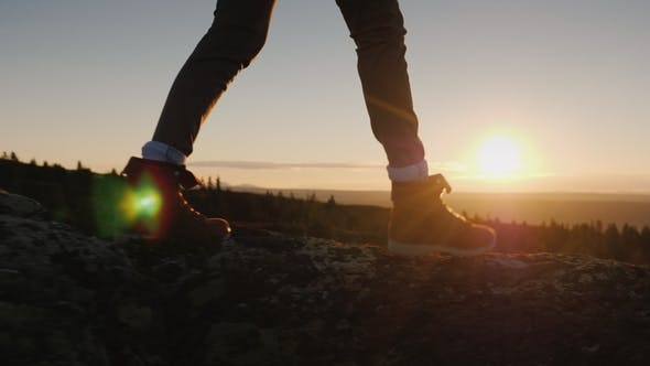 Cover Image for Legs in Trekking Boots Go Along the Mountain Ridge Against the Backdrop of the Rising Sun. Travel
