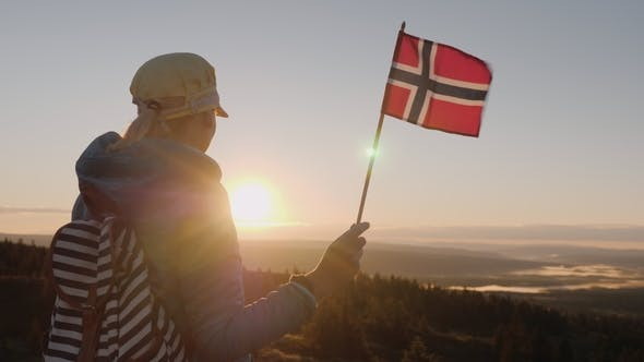 Thumbnail for A Traveler with the Flag of Norway in His Hand Meets the Sunrise on the Top of the Mountain. Enjoys