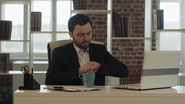 Cover Image for Businessman with a Laptop and Tea Looking at His Watch