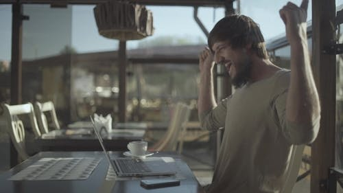 Excited Beard Man Celebrating Success While Working on Laptop. RAW Ungraded