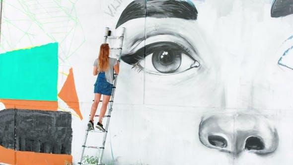 Thumbnail for Girl Making Graffiti of Big Female Face with Aerosol Spray on Urban Street Wall