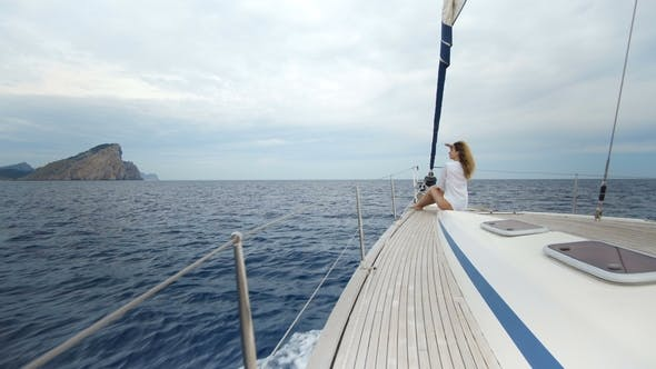 Thumbnail for Beautiful Young Woman in White on the Bow of Yacht
