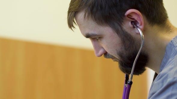 Thumbnail for Young Bearded Doctor Listen Heartbeating of Patieent with Stethoscope