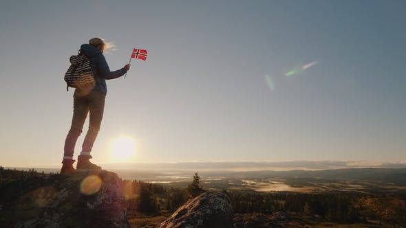 Thumbnail for A Woman Stands on Top of a Mountain Holding the Flag of Norway in Her Hand