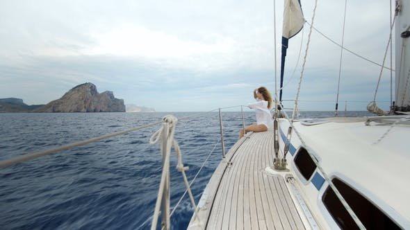 Thumbnail for Beautiful Girl in the Swimsuit Sits on the Bow of the Yacht and Sunbaths in the Sea