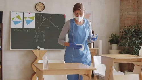 Cleaning Lady Disinfecting and Wiping School Desks in Classroom
