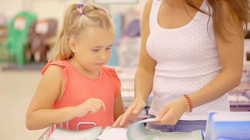 Portrait of Mom and Cute Blonde Little Daughter Buying Stationeries for School