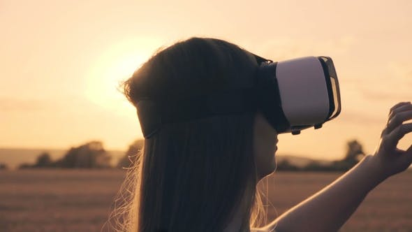 Thumbnail for Beautiful Girl in a Golden Wheat Field Uses Virtual Reality Glasses in the Sunset