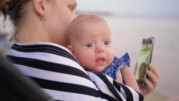 Mother with Baby Video Chatting on Cellphone at the Beach