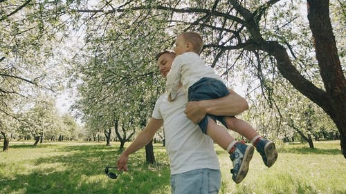 Father and Son Playing at Park. Father Raises Child in Arms. Fatherhood Concept