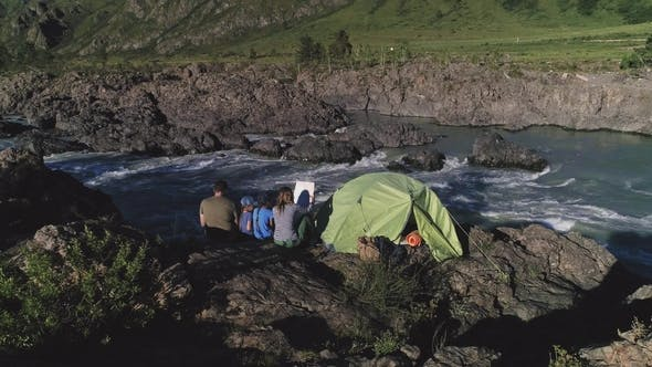 Cover Image for Family of Travelers with Children Sit Near a Tent and Enjoy a View of the Mountain River
