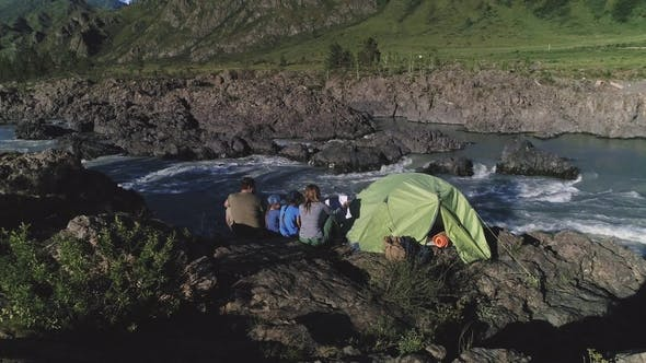 Cover Image for Aerial. A Family of Travelers with Children Sit Near a Tent and Enjoy a View of the Mountain River