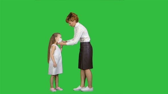 Thumbnail for Young Mother Put on Medical Mask To Her Little Girl on a Green Screen, Chroma Key