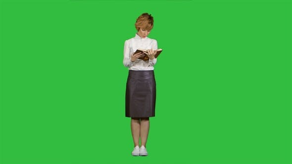 Thumbnail for Woman Standing and Reading Book on a Green Screen, Chroma Key