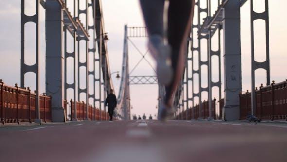 Thumbnail for Slim Senior Female Running Across Bridge in City