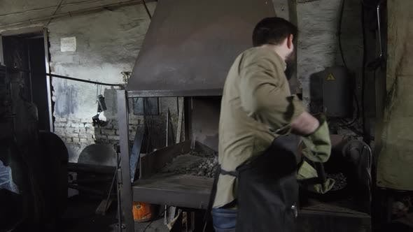 Thumbnail for Blacksmith Putting New Coals into Furnace