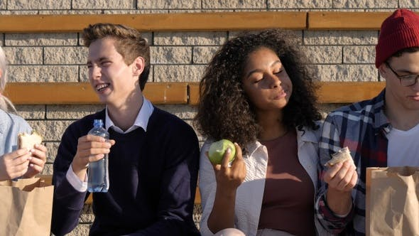 Thumbnail for Multiracial happy young people eating outdoors.