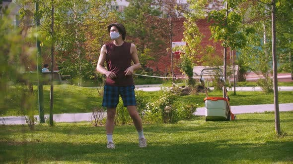 Thumbnail for A Young Man in Medical Mask Running in the Park and Starts Warming Up